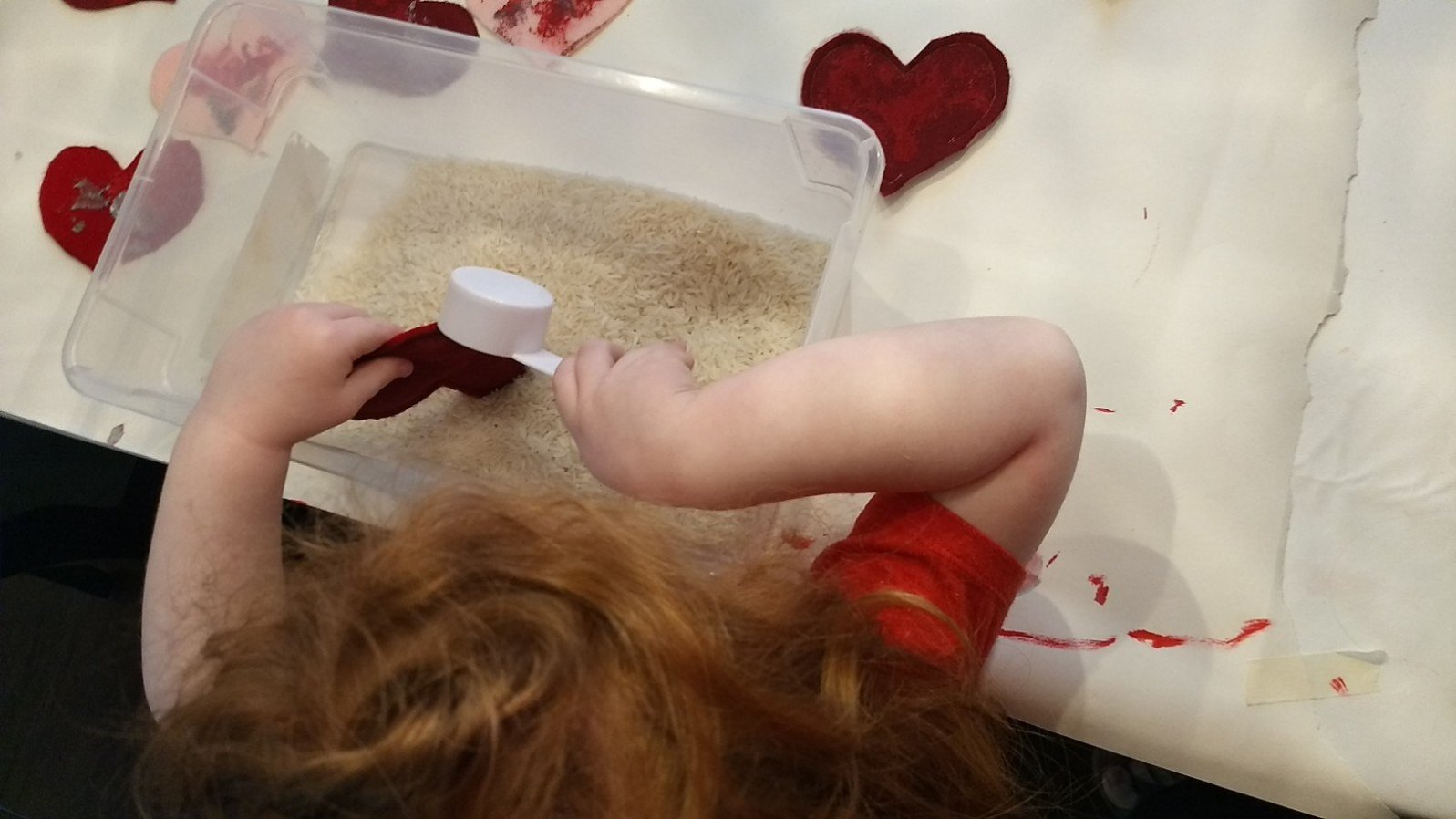 Child fills felt pouches with rice to make hand warmers