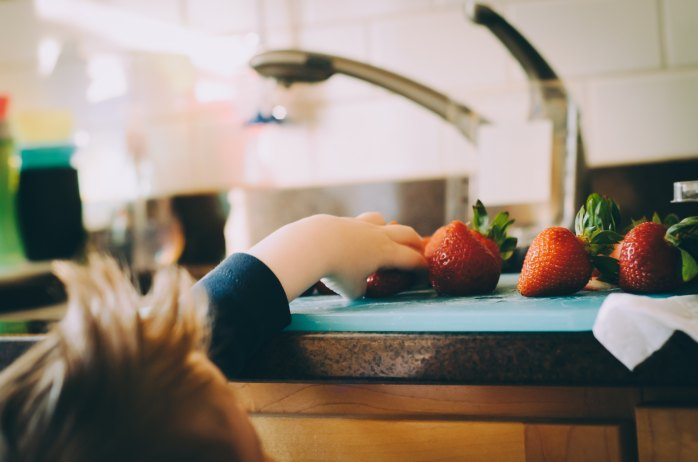 Child reaches for freshly-washed berries in a warm, supportive home environment.